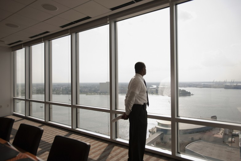 African American businessman looking out office window --- Image by © Mark Edward Atkinson/Blend Images/Corbis