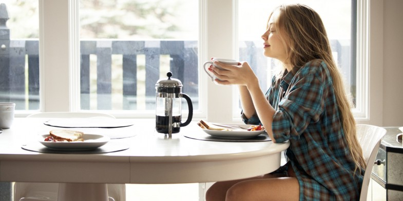 Young Woman Enjoying Coffee And Breakfast