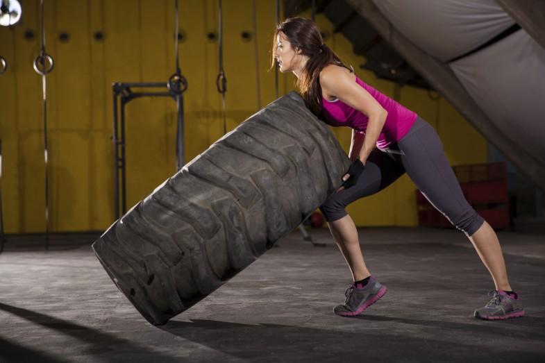 Cute girl flipping a tire