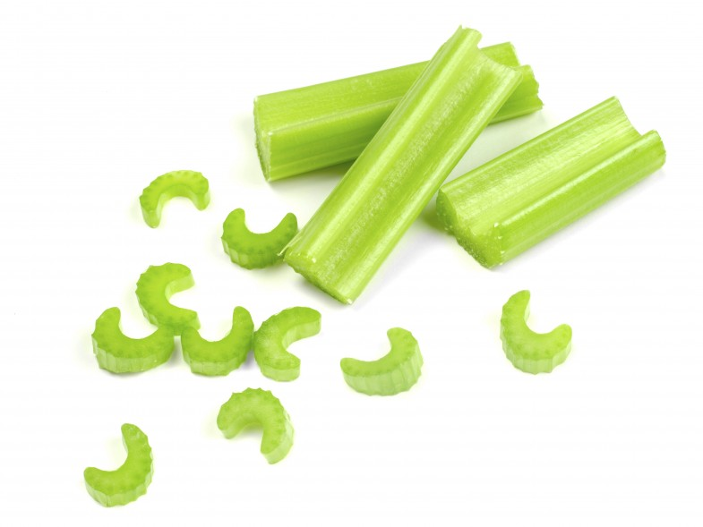 Sticks of celery with chopped pieces, isolated on white background. Light shadows around each piece.