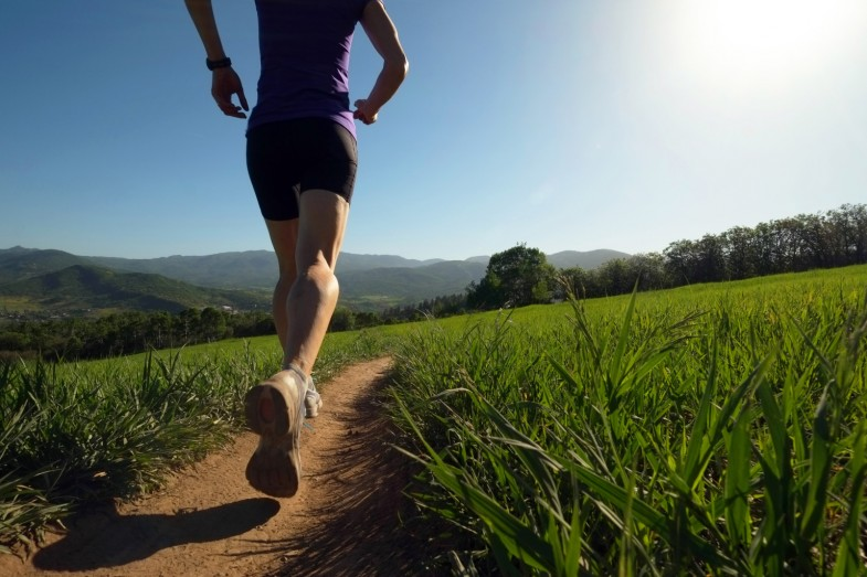 Woman running on trail thru meadow
