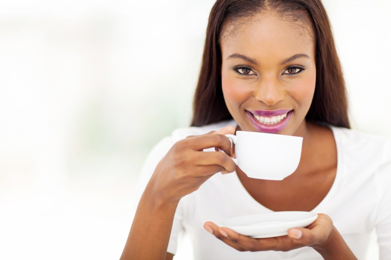 beautiful african american woman drinking coffee at home